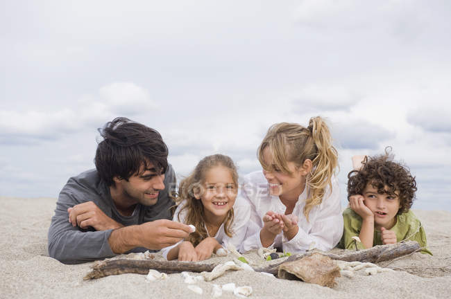 Happy family relaxing on beach, lying in sand with seashells — Stock Photo