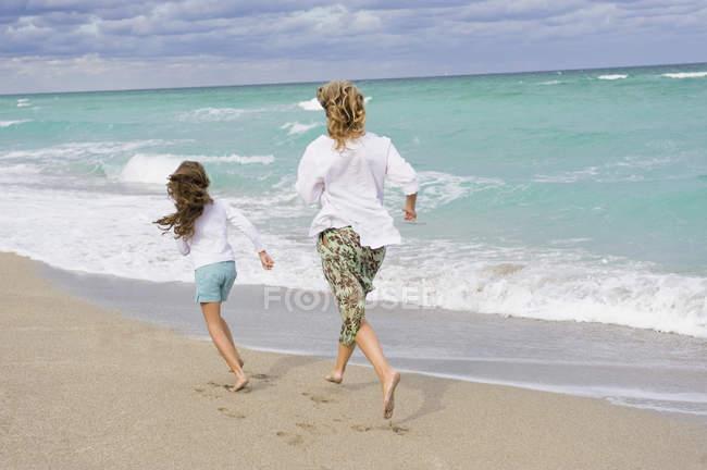 Жінка біжить з дочкою на піщаному пляжі — стокове фото