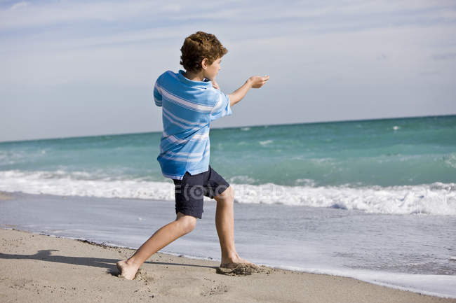 Boy throwing a stone into sea on beach — Stock Photo