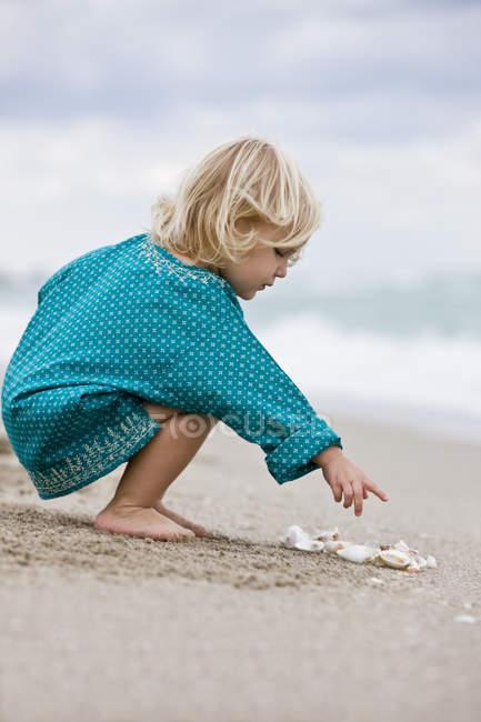 Bambina che gioca con conchiglie sulla spiaggia — Foto stock