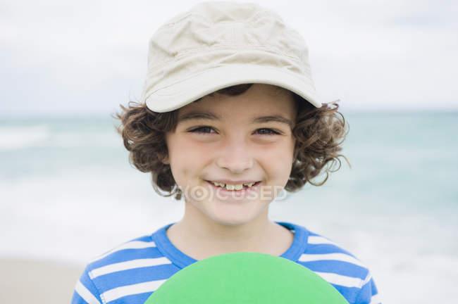 Garçon jouer avec plastique frisbee sur la plage — Photo de stock