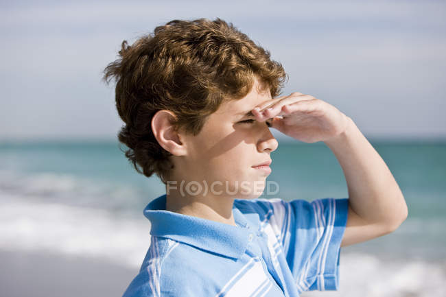 Close-up of boy standing on beach and looking at sea — Stock Photo