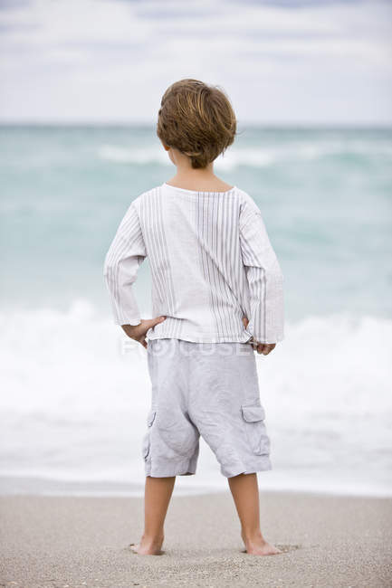 Rear view of little  boy standing on beach and looking at sea — Stock Photo