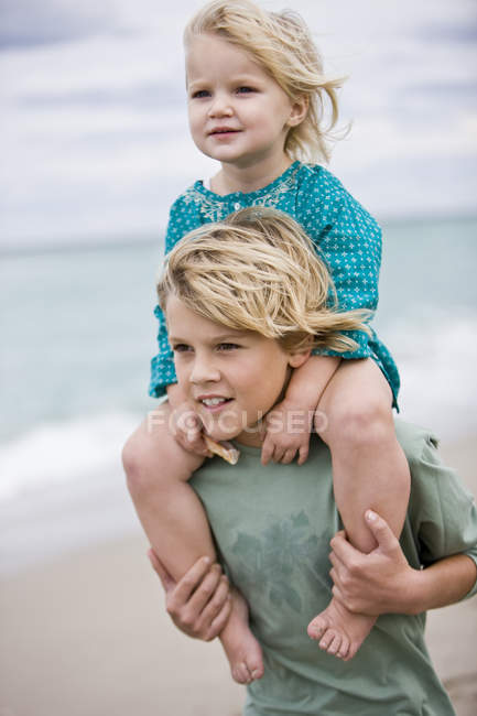 Boy carrying sister on shoulders on beach — Stock Photo