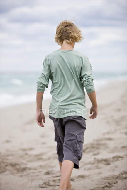 Rear view of boy walking on sandy beach under cloudy sky — Stock Photo
