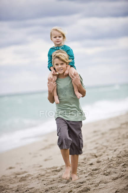 Boy carrying sister on shoulders on beach — стоковое фото
