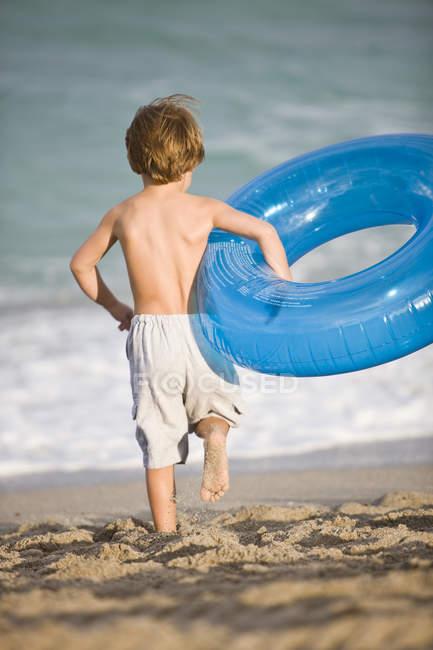 Маленький мальчик с надувным кольцом на пляже — стоковое фото