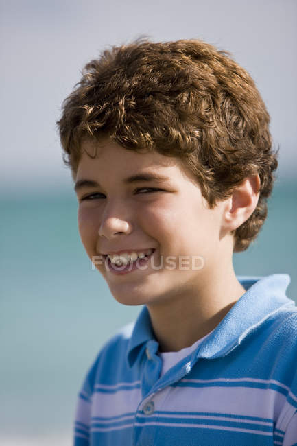 Portrait of curly boy smiling outdoors — Stock Photo
