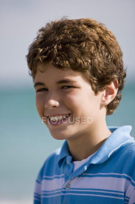 Portrait de garçon bouclé souriant à l'extérieur — Photo de stock