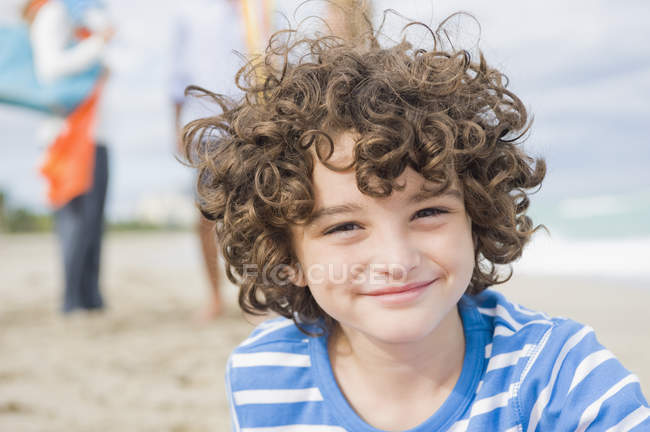 Portrait of smiling boy with curly hair outdoors — Stock Photo