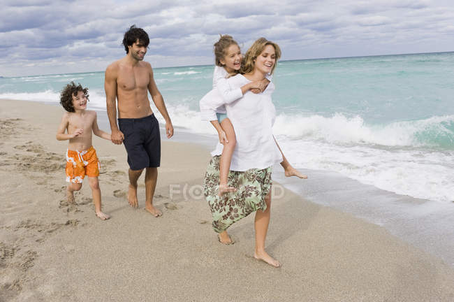 Family with kids enjoying vacations on sandy beach — Stock Photo