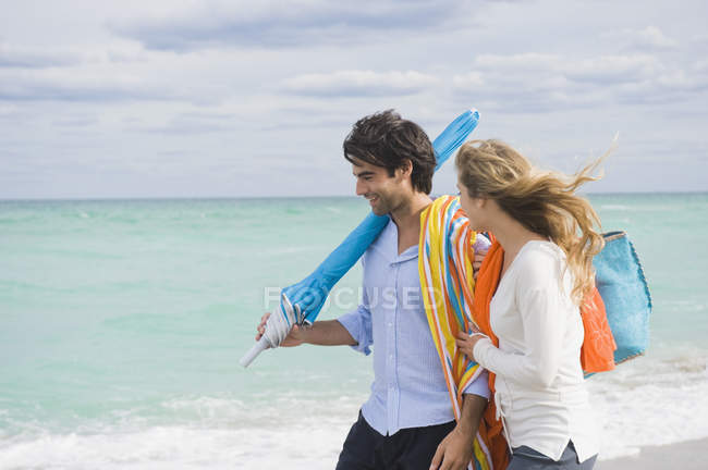 Couple walking on beach with bag and umbrella under cloudy sky — Stock Photo