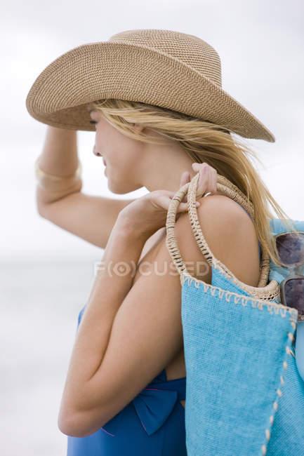 Donna in cappello borsa da trasporto sulla spiaggia — Foto stock