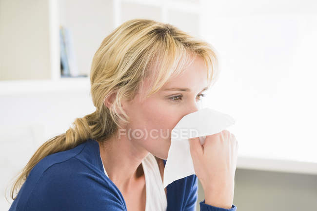 Close-up of woman blowing nose with handkerchief — Stock Photo