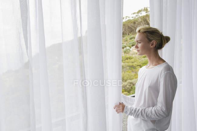 Serena giovane donna in piedi sul balcone e guardando la vista — Foto stock