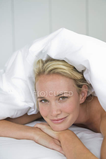 Close-up of woman lying on bed under duvet and smiling — Stock Photo