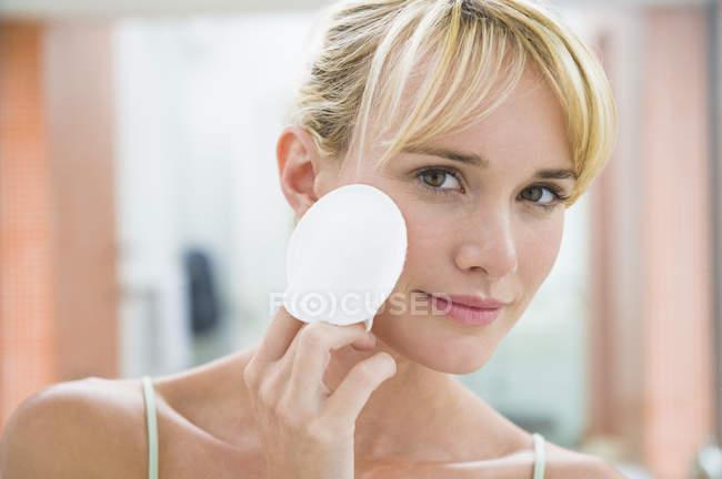 Молодая женщина, применяя пудра с ватным тампоном — стоковое фото