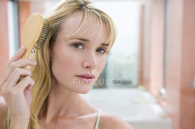 Young blond woman brushing hair in bathroom — Stock Photo