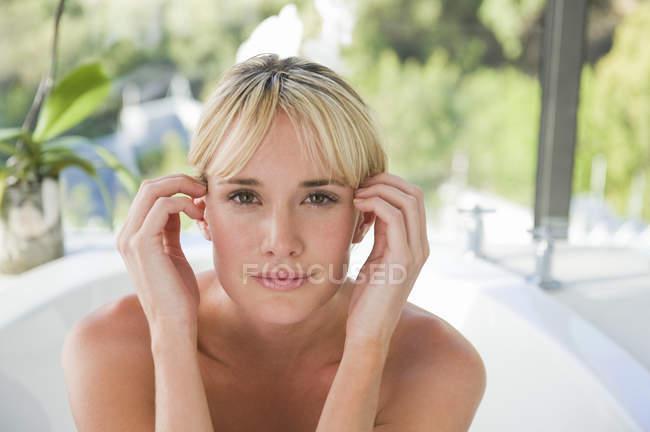 Портрет молодой блондинки в ванной с садом на заднем плане — стоковое фото