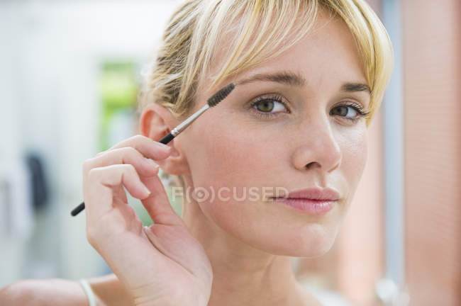 Close-up of blond young woman using eyebrow brush — Stock Photo