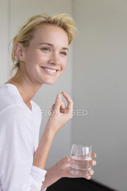 Souriante jeune femme prenant capsule oméga-3 et en tenant le verre d'eau — Photo de stock