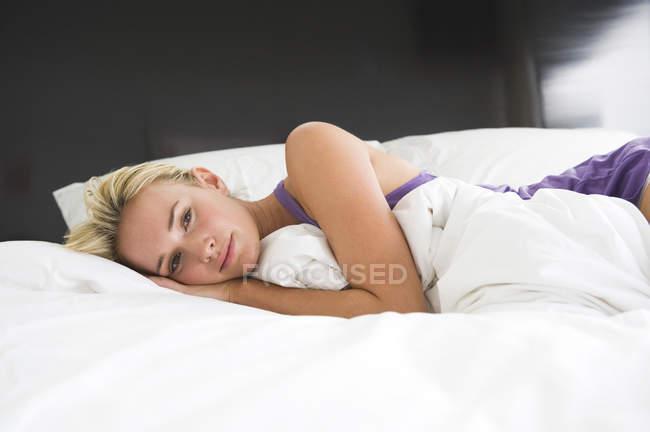 Porträt einer sinnlichen jungen Frau, die auf dem Bett liegt — Stockfoto