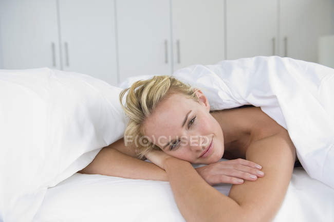 Nahaufnahme einer verträumten Frau, die auf dem Bett liegt und wegschaut — Stockfoto