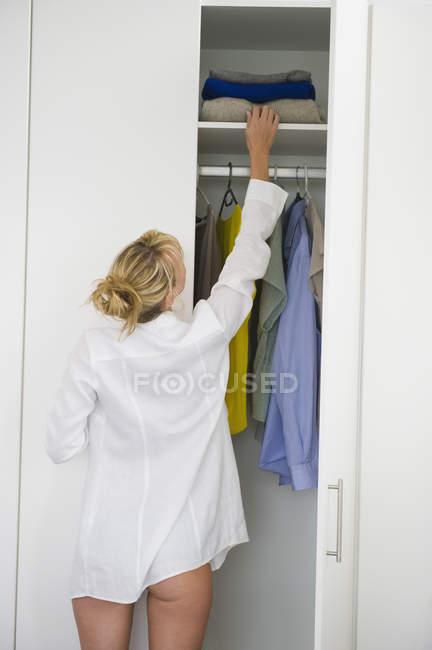 Mulher selecionando roupas em guarda-roupa em casa — Fotografia de Stock