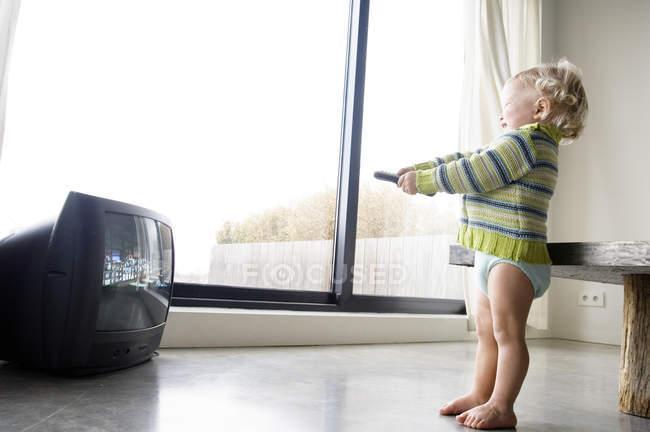 Petit garçon tenant la télécommande du téléviseur à la maison — Photo de stock