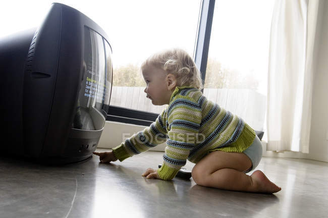 Little baby boy turning on TV while sitting on floor at home — Stock Photo