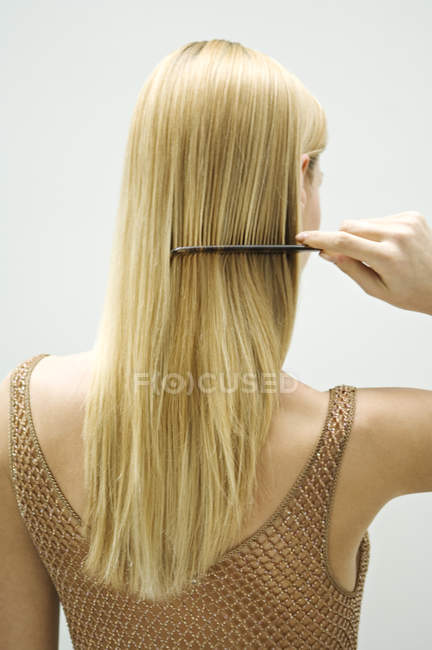 Rear view of blond woman combing hair — Stock Photo