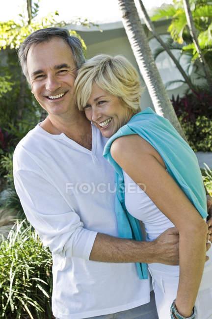 Ritratto di coppia sorridente abbracciata in giardino — Foto stock