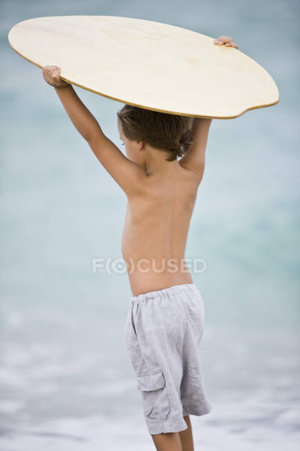 Rear view of little boy holding a body board over head on beach — Stock Photo