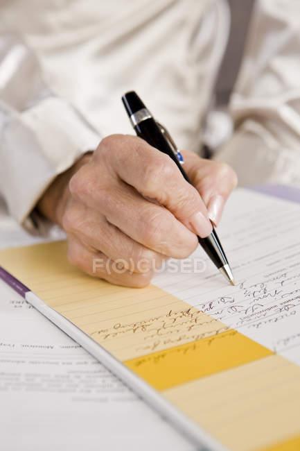 Close-up da mão feminina, preenchendo o formulário de candidatura — Fotografia de Stock