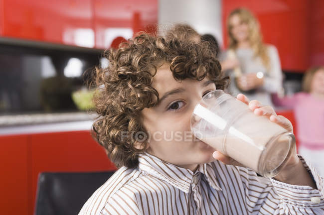 Portrait of boy drinking milk from glass in kitchen — Stock Photo