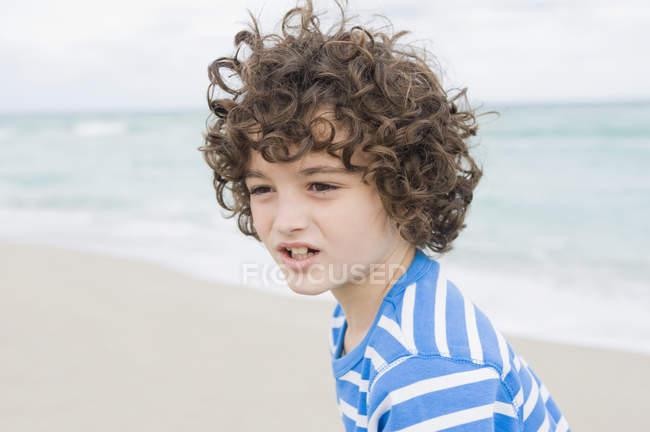 Garçon réfléchi avec les cheveux bouclés sur la plage — Photo de stock