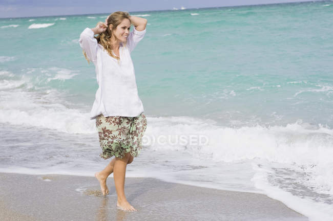Smiling young woman walking on beach with hands in hair — Stock Photo