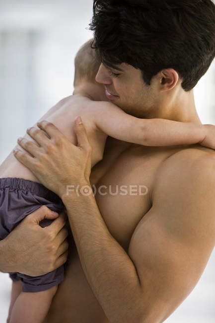 Shirtless young man carrying little son — Stock Photo