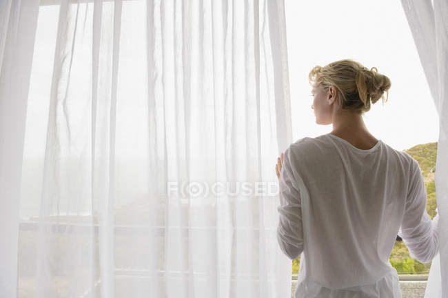 Vista posteriore della donna in piedi sul balcone e guardando la vista — Foto stock