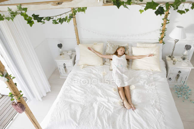 Innocent little girl sleeping on bed decorated with leaves — Stock Photo