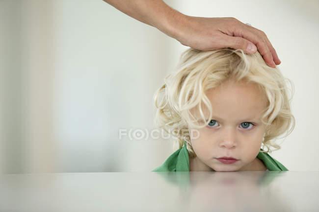 Primo piano della mano umana sulla testa della figlia bionda — Foto stock