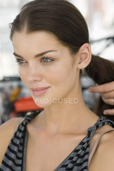 Hand of hairdresser arranging hair of attractive model — Stock Photo