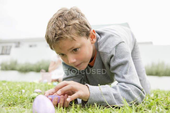 Мальчик смотрит на пасхальное яйцо, стоя на траве на коленях — стоковое фото