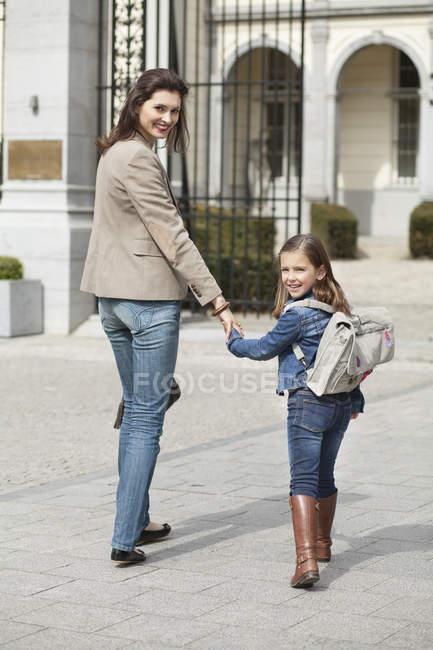 Menina de sorriso com a matriz que anda à escola — Fotografia de Stock