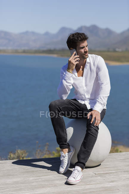 Man sitting on stone ball and talking on mobile phone in nature — Stock Photo