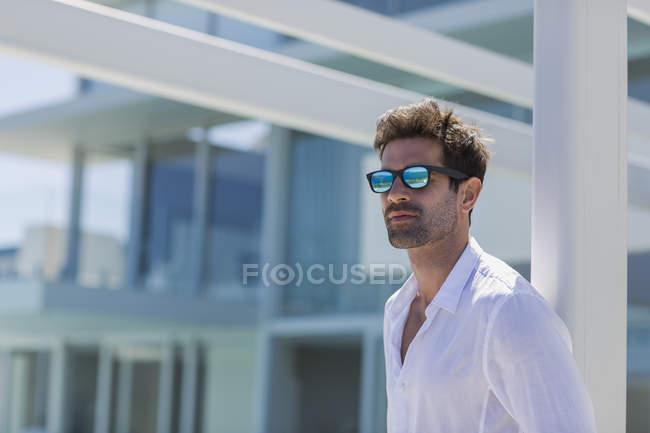 Gros plan d'un homme élégant et confiant portant des lunettes de soleil devant un bâtiment moderne — Photo de stock