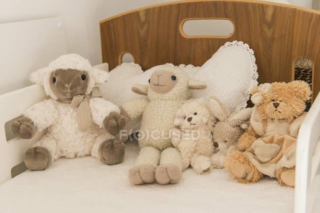 Закри опудала милі іграшки на ліжку в спальні дитини — стокове фото
