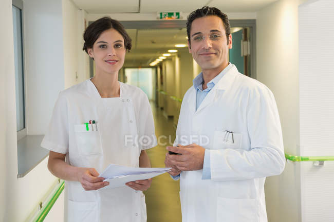 Doctor and nurse smiling in hospital corridor — Foto stock
