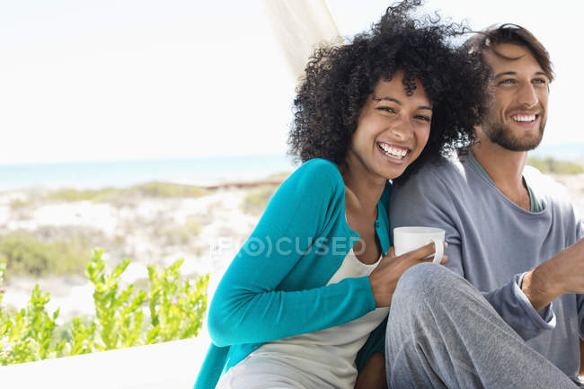 Portrait of laughing young couple resting on coast — Stock Photo