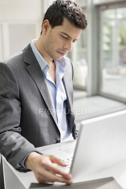 Young businessman working on laptop in office — Stock Photo